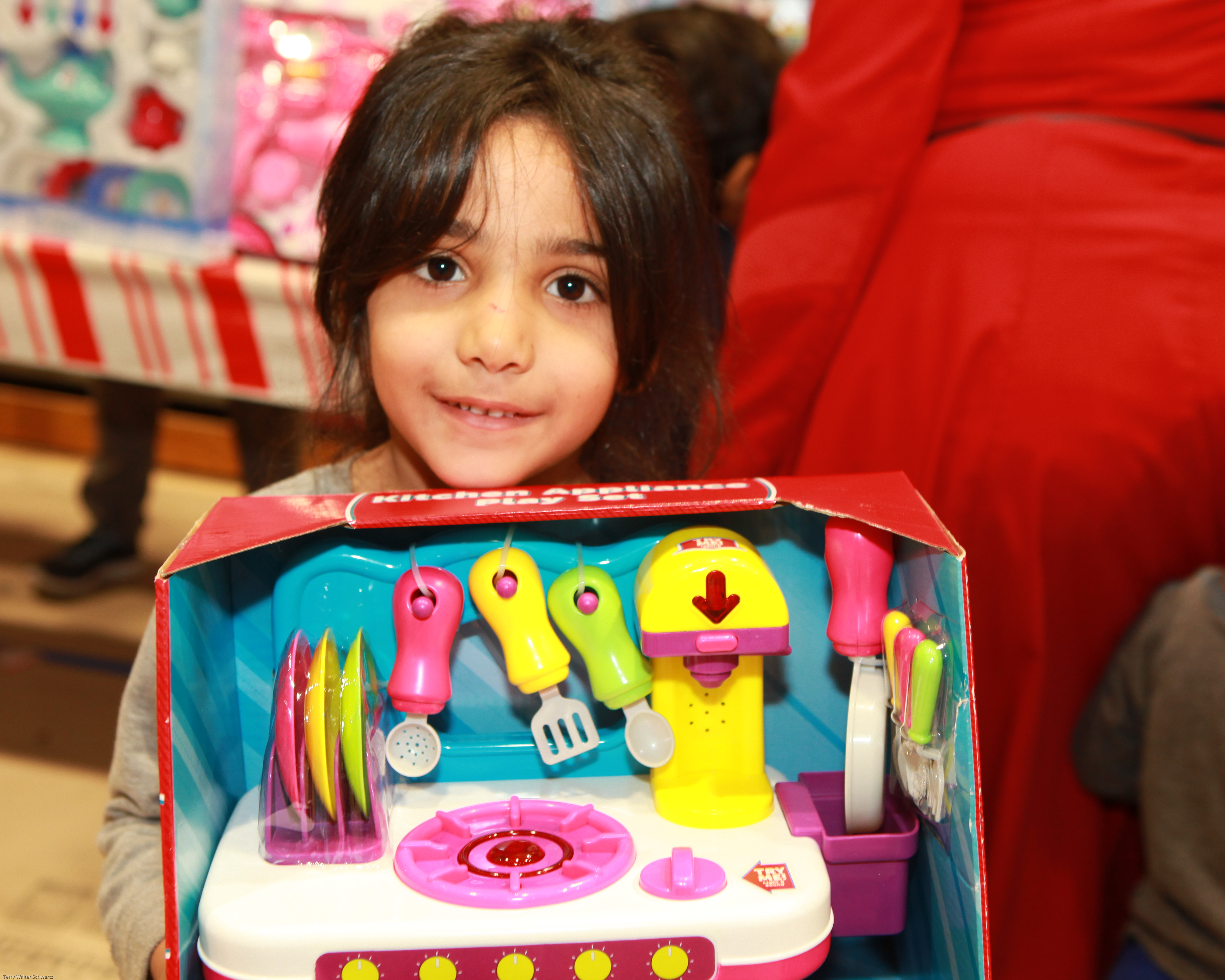 Smiling girl holding a toy cooking set